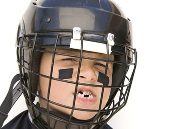 a child with a helmet and knocked out teeth