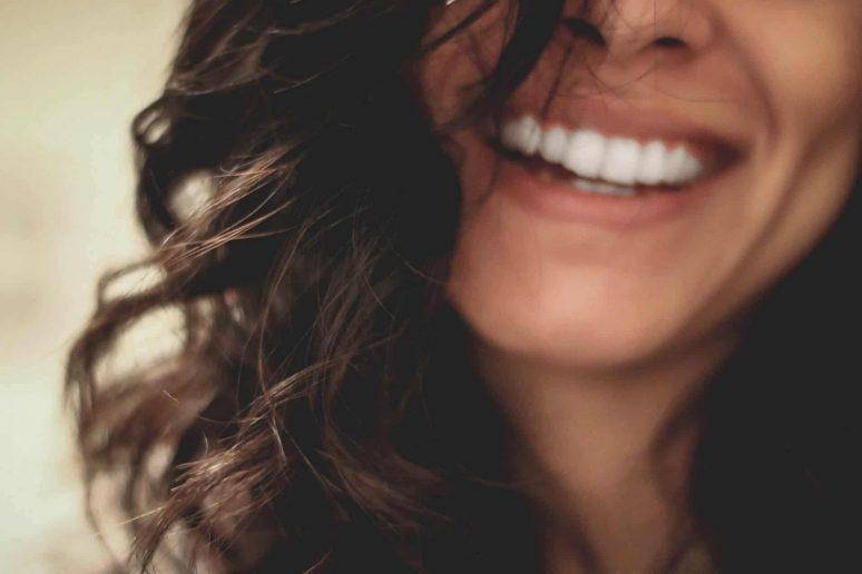 Faded photo of a woman smiling with her teeth after a visit to the dentist