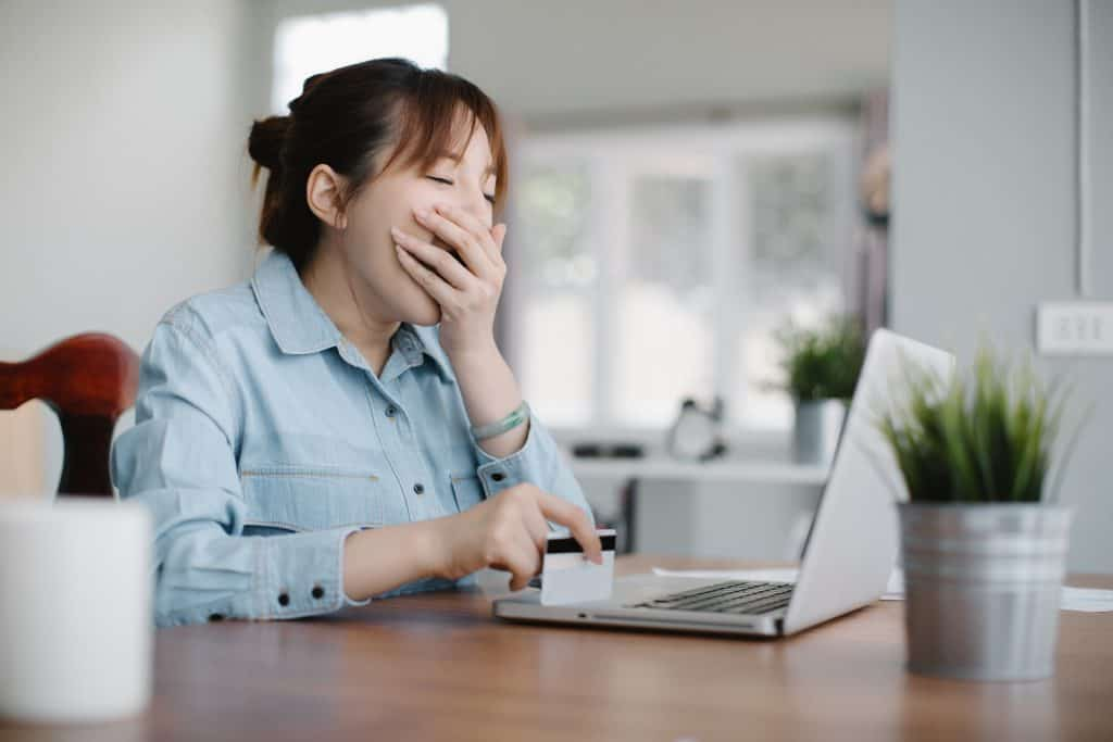 a woman yawning while using a laptop
