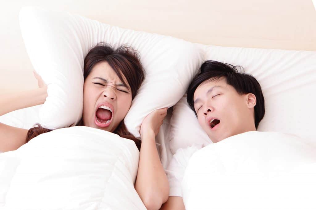 man snoring at night and disturbing his partner