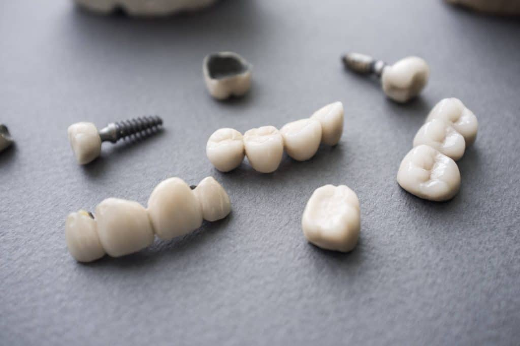 Ceramic dentures and crowns on gray background