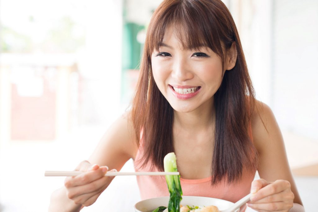 Asian girl eating vegetable noodles at Chinese restaurant. Young woman living lifestyle.