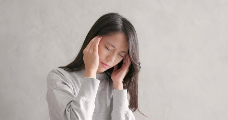woman having a headache from teeth grinding